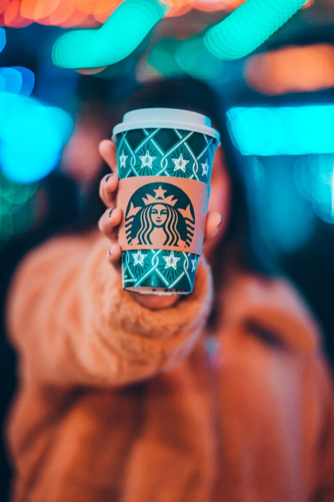 person holding Starbucks cup towards camera