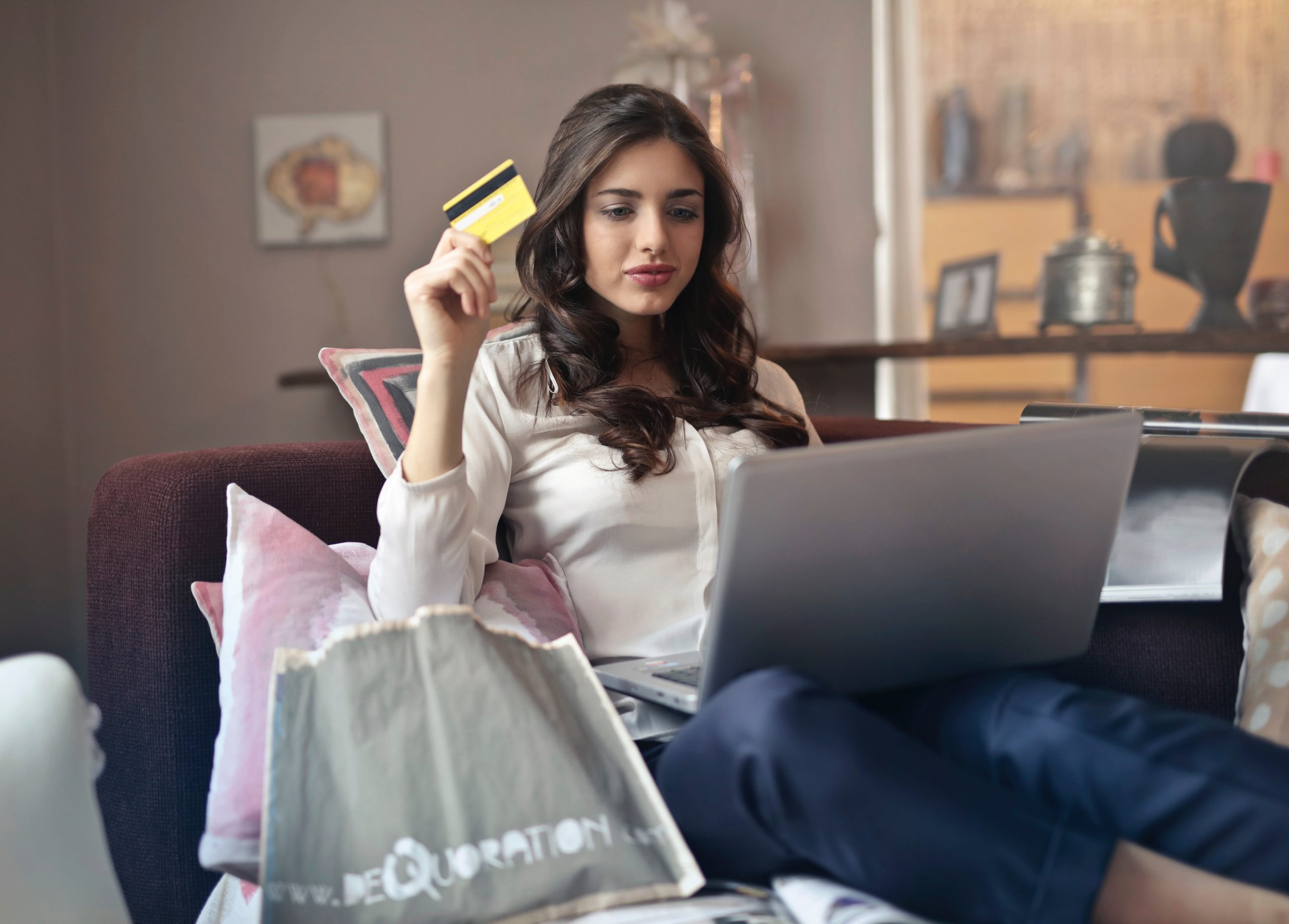 woman-holding-credit-card-while-operating-silver-laptop