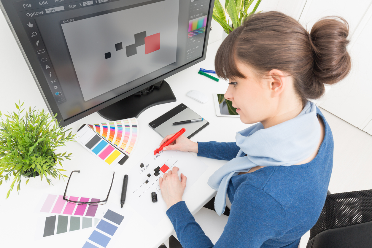 Graphic designer at work with color swatch samples creating logo on computer screen