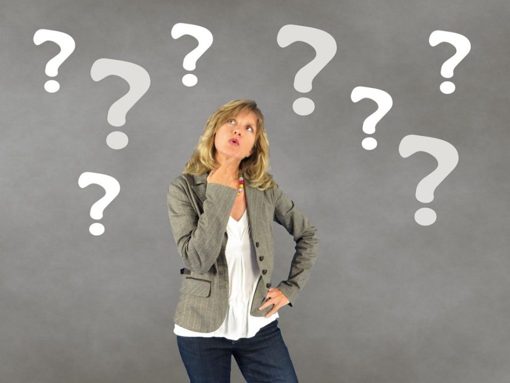 woman thinking of what to ask with question marks around