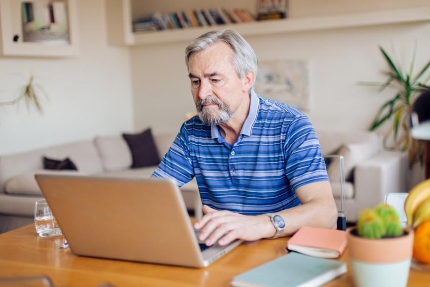 man-wearing-blue-shirt-sitting-using-laptop-computer