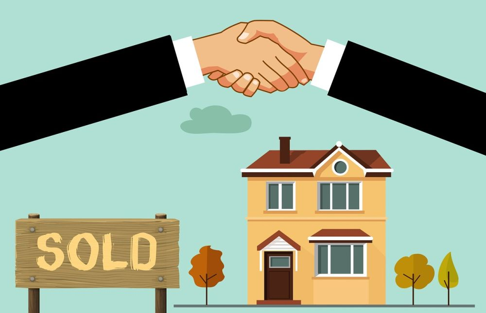 real estate buyer and seller handshaking with a sold house