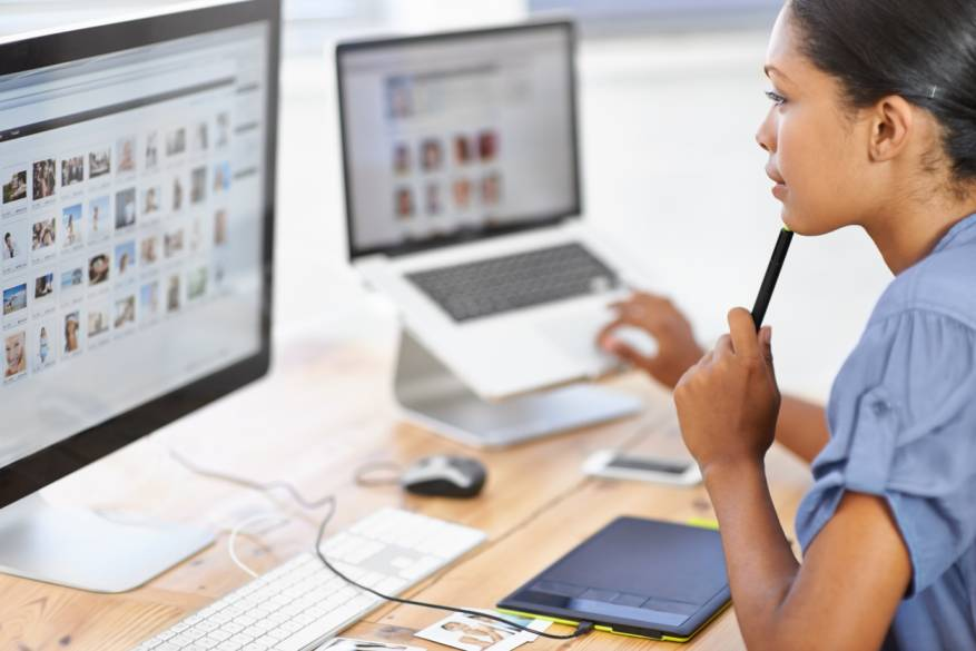 woman pen on left hand viewing images desktop laptop computer
