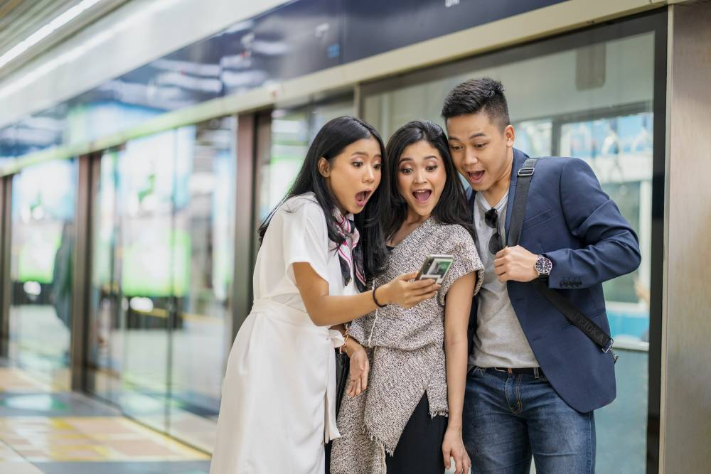 three excited people using social media app on mobile phone