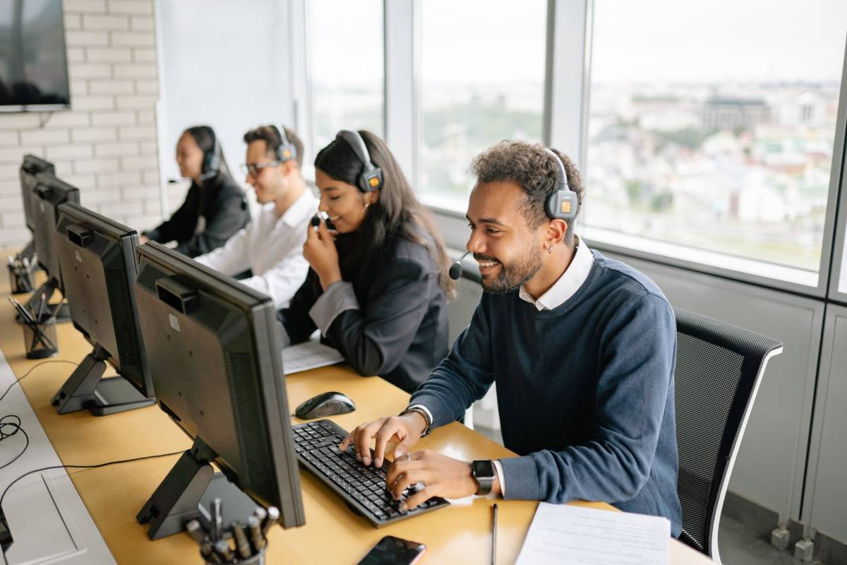 call center agents wearing headset while calling leads using office computer